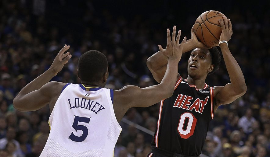 Miami Heat guard Josh Richardson, right, shoots against Golden State Warriors' Kevon Looney (5) during the first half of an NBA basketball game Monday, Nov. 6, 2017, in Oakland, Calif. (AP Photo/Ben Margot)