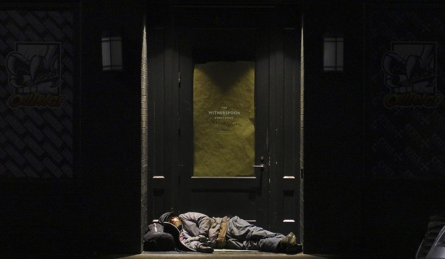 A man sleeps in a doorway in downtown Portland, Ore., on Sept. 19, 2017. On any given night, and often during the day, dozens of people sleep or camp on the sidewalks and parks of the downtown area, as the rising crisis of homelessness becomes more visible. (AP Photo/Ted S. Warren)