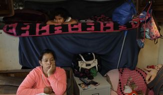 In this photo taken Oct. 5, 2017, Delmi Ruiz, bottom, sits inside and RV where here family lives and sleeps under her daughter Delmi, 4, top, in Mountain View, Calif. The Ruiz Hernandez family was left homeless after the landlord in the apartment they rented hiked their rent beyond what they could afford. The booming economy along the West Coast has led to an historic shortage of affordable housing and has upended the stereotypical view of people out on the streets. (AP Photo/Marcio Jose Sanchez)