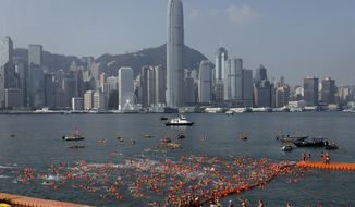 FILE - In this Sunday, Oct. 29, 2017 file photo, competitors swim during the annual 1-kilometer (0.6-mile) harbor race at the Victoria Harbour in Hong Kong. Hong Kong is set to retain its status as the city most visited by international travelers this year in spite of strained relations with mainland China. In a report published Tuesday, Nov. 7, market research firm Euromonitor International said it estimates 25.7 million arrivals in Hong Kong this year, down 3.2 percent on 2016. (AP Photo/Vincent Yu, file)