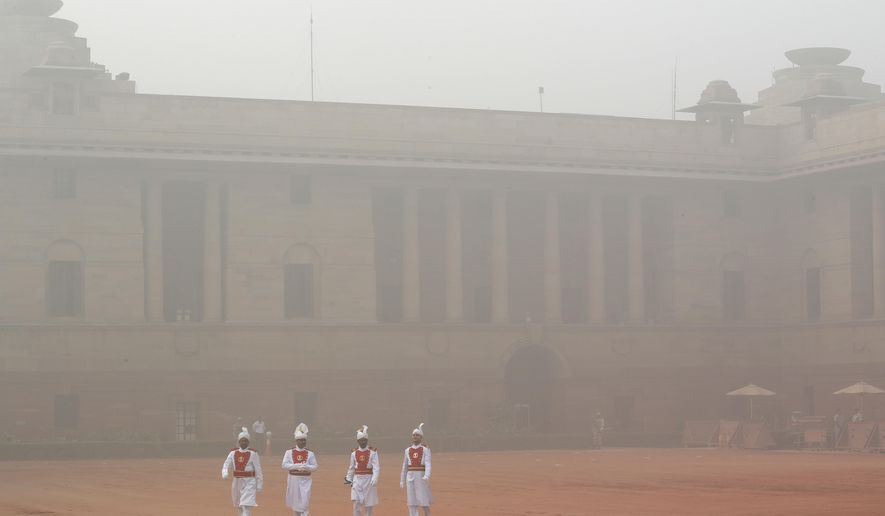 Indian presidential staff members walk surrounded by smog at the presidential palace in New Delhi, India, Tuesday, Nov. 7, 2017. Air pollution in India's capital has hit hazardous levels prompting local officials to ask that school shut down and a half marathon scheduled later in November be called off. (AP Photo/Manish Swarup)
