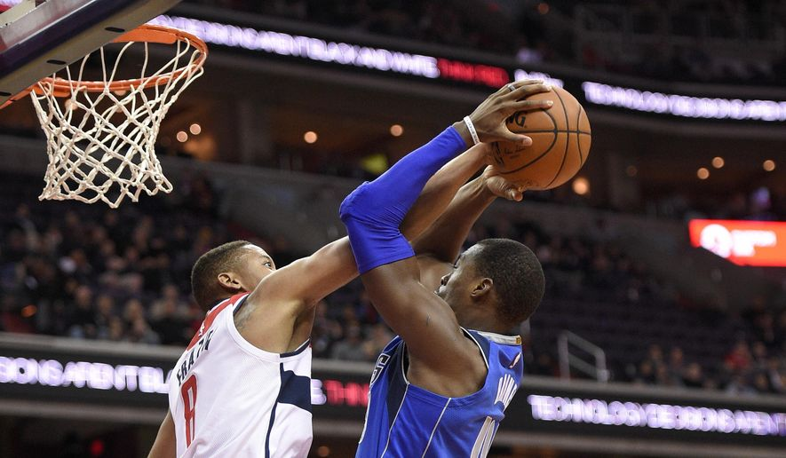 Washington Wizards guard Tim Frazier, left, fouls Dallas Mavericks forward Harrison Barnes, right, during the first half of an NBA basketball game, Tuesday, Nov. 7, 2017, in Washington. Also seen is Wizards forward Kelly Oubre Jr. (12). (AP Photo/Nick Wass)