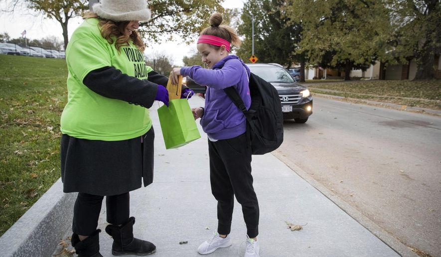 In a Wednesday Nov. 1, 2017, volunteer ballot collector Michelle Hankins collects ballots for the tax-levy override election from fifth-grader Tinley Engel outside Montclair Elementary School  in Omaha, Neb. Some volunteers have been stationed outside Millard Public Schools to collect marked-up mail-in ballots for the levy override election that ends Nov. 14. The collection of ballots in this manner is illegal in some states and is drawing the concern of a local legislator. (Brendan Sullivan/The World-Herald via AP)