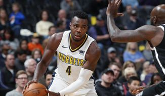 Denver Nuggets forward Paul Millsap, left, drives to the basket as Brooklyn Nets forward Quincy Acy defends in the first half of an NBA basketball game Tuesday, Nov. 7, 2017, in Denver. (AP Photo/David Zalubowski)