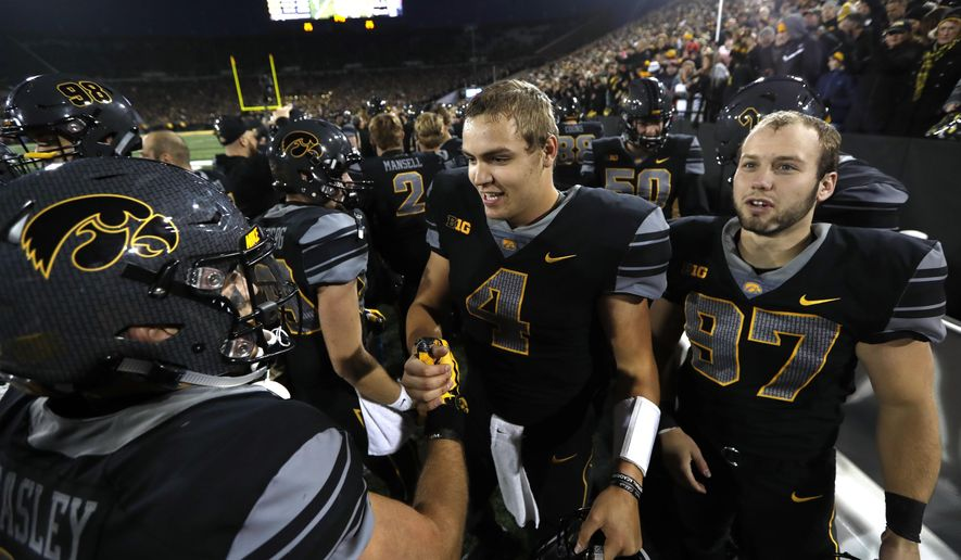 Iowa quarterback Nathan Stanley (4) and Tyler Kluver, right, celebrate with teammate Nick Easley, left, after an NCAA college football game against Ohio State, Saturday, Nov. 4, 2017, in Iowa City, Iowa. (AP Photo/Charlie Neibergall)