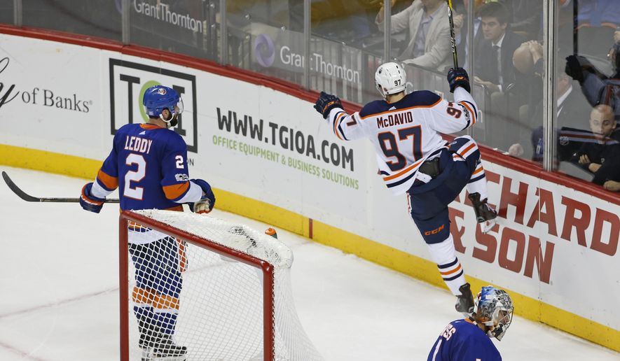New York Islanders Nick Leddy, left, and and Islanders goalie Thomas Greiss (1) of Germany skate off as Edmonton Oilers center Connor McDavid (97) celebrates his game-winning overtime goal in the Oilers 2-1 victory over the Islanders in an NHL hockey game in New York, Tuesday, Nov. 7, 2017. (AP Photo/Kathy Willens)