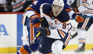 Edmonton Oilers center Connor McDavid (97) and New York Islanders defenseman Thomas Hickey (14) keep their eyes on the puck during the first period of an NHL hockey game in New York, Tuesday, Nov. 7, 2017. (AP Photo/Kathy Willens)