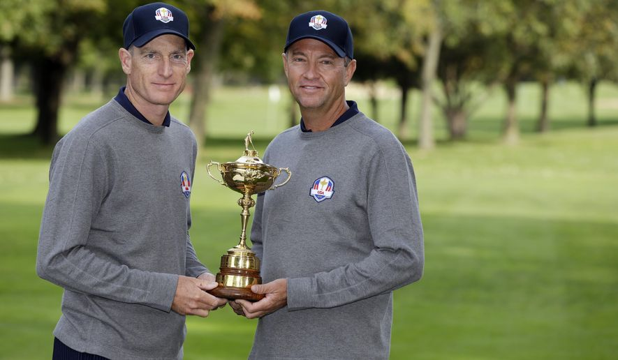FILE - In this Sept. 25, 2012, file photo, USA's Ryder Cup captain Davis Love III, left, and player Jim Furyk pose with the Ryder Cup trophy during the Ryder Cup golf tournament, at the Medinah Country Club in Medinah, Ill. The Americans have a system where the same players are serving as captains or assistants at the Ryder Cup. (AP Photo/Chris Carlson, File)
