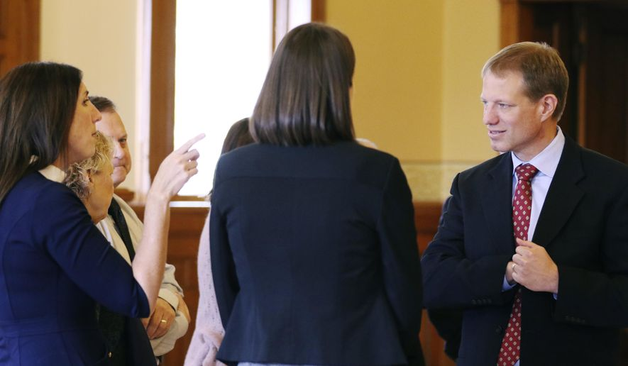 Charles Crueger with Crueger Dickinson law firm speaks with associates Tuesday, Nov. 7, 2017, at the old courthouse museum in West Bend, Wis during a press conference announcing 28 counties in Wisconsin have filed lawsuits against pharmaceutical companies. Attorney Erin Dickinson with Crueger Dickinson law firm stated the counties would be looking to recoup monies to pay for services designed to help opioid addicts.  (John R. Ehlke/West Bend Daily News via AP)