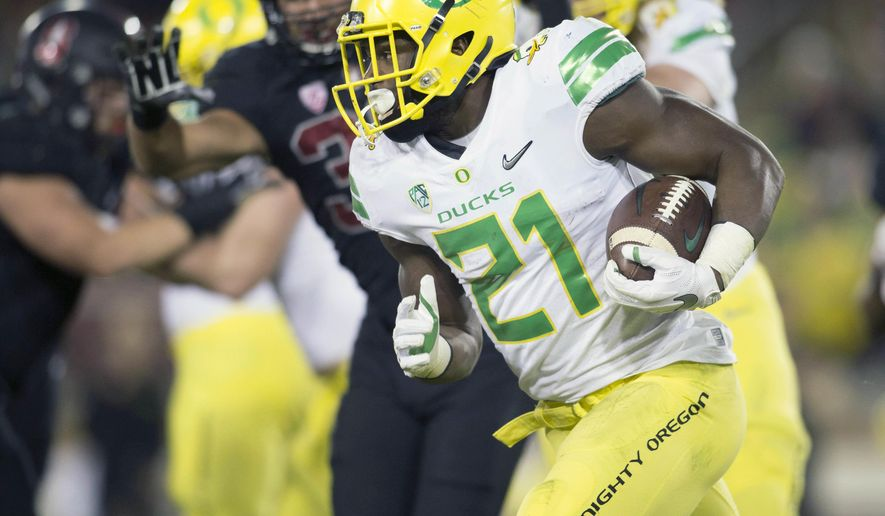 FILE - In this Saturday, Oct. 14, 2017 file photo, Oregon's Royce Freeman (21) takes the ball around left end against Stanford during the third quarter of an NCAA college football game in Stanford, Calif. Freeman is among several seniors across the Pac-12 who stayed with their college teams rather than departing for the NFL. For some of them, like Freeman, the decision is paying off. (AP Photo/D. Ross Cameron, File)