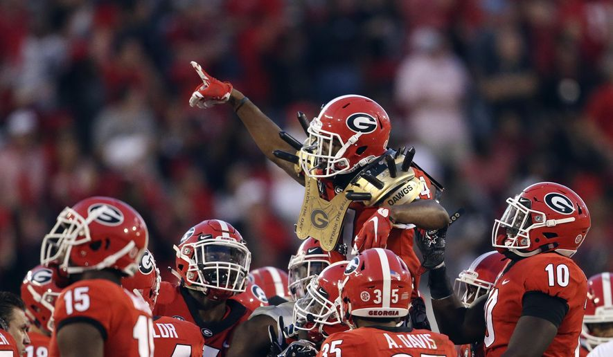 "FILE - In this Nov. 4, 2017, file photo, Georgia defensive back Malkom Parrish (14) wears the ""Dawg Spikes"" as he is carried off the field after intercepting a pass in the closing moments of the team's NCAA college football game against South Carolina in Athens, Ga. Georgia won 24-10. Georgia, Alabama, Notre Dame and Clemson held their spots in the top four of the College Football Playoff rankings, and unbeaten Miami moved up three spots to No. 7 before its showdown with the Fighting Irish. (AP Photo/John Bazemore, File) **FILE**"