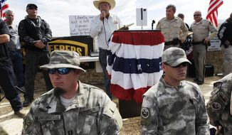 FILE - In this April 12, 2014, file photo rancher Cliven Bundy, top center, addresses his supporters along side Clark County Sheriff Doug Gillespie, right, while being guarded by self-described militia members in the foreground. Twice federal prosecutors in Las Vegas have failed to win full convictions of men who had guns during an April 2014 armed standoff with government agents trying to round up cattle belonging to Nevada rancher Cliven Bundy. Nevertheless, they're now moving to the main event, with openings expected Tuesday, Nov. 7  for a trial of the 71-year-old family patriarch and states' rights figure, his two eldest sons and one other co-defendant accused of leading a self-styled militia in an uprising against government authority. (Jason Bean/Las Vegas Review-Journal via AP, File)/Las Vegas Review-Journal via AP)/Las Vegas Review-Journal via AP)