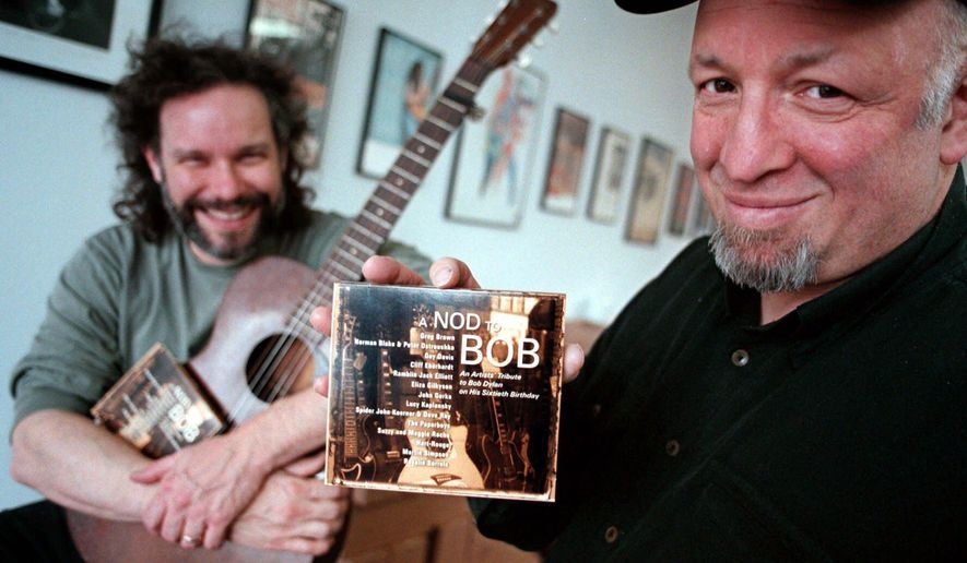 FILE - In this April 10, 2001 file photo, Red House Records President Bob Feldman displays a CD tribute as musician John Gorka, left, looks on at the Red House Records offices in St. Paul, Minn. Red House Records has been sold to Compass Records Group of Nashville. The sale was announced Tuesday. (AP Photo/Dawn Villella, File)