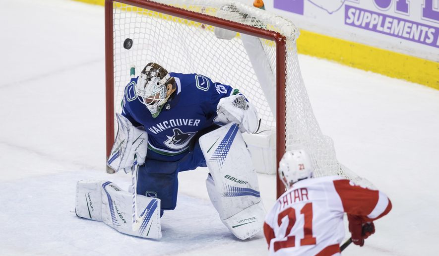 Detroit Red Wings' Tomas Tatar, bottom, of Slovakia, scores the winning goal against Vancouver Canucks' goalie Jacob Markstrom, of Sweden, during the third period of an NHL hockey game in Vancouver, British Columbia, Monday, Nov. 6, 2017. (Darryl Dyck/The Canadian Press via AP)