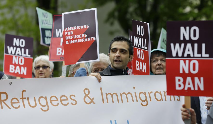 FILE - In this May 15, 2017 file photo, protesters hold signs during a demonstration against President Donald Trump's revised travel ban, outside a federal courthouse in Seattle. A Somali refugee living in Washington state is asking a federal judge to let his wife and young children join him in the U.S., saying the Trump administration's indefinite ban on allowing the families of refugees to enter the country violates immigration law. (AP Photo/Ted S. Warren, File)