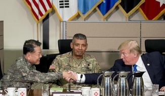U.S. President Donald Trump, accompanied by United States Forces Korea Commander Gen. Vincent Brooks, center, shakes hands with South Korean Gen. Kim Byung-joo during an operational briefing at the eighth Army Operational Command Center at Camp Humphreys in Pyeongtaek, South Korea, Tuesday, Nov. 7, 2017. Trump is on a five-country trip through Asia traveling to Japan, South Korea, China, Vietnam and the Philippines. (AP Photo/Andrew Harnik) ** FILE **