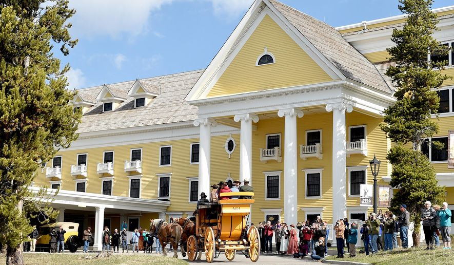 FILE - In this May 13, 2016 file photo, the historic yellow stagecoach arrives at the Lake Yellowstone Hotel as the crowd takes photos during the 125th anniversary celebration of the hotel. A legislative panel is considering a new tax to help fund Wyoming's tourism promotion efforts. The Legislature's Joint Revenue Committee on Tuesday, Nov. 7, 2017 is drafting a bill that would impose a 1 percent tax at hotels, restaurants, bars and other leisure and hospitality establishments around the state. (Hannah Potes/The Billings Gazette via AP, File)
