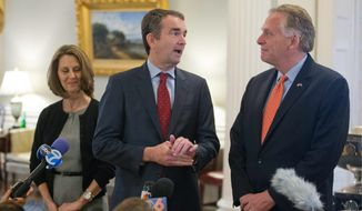 Virginia Gov. Terry McAuliffe (right) listened to Gov.-elect, Ralph Northam as Pam Northam looked on during a news conference in the governor's mansion in Richmond on Wednesday. (Associated Press)