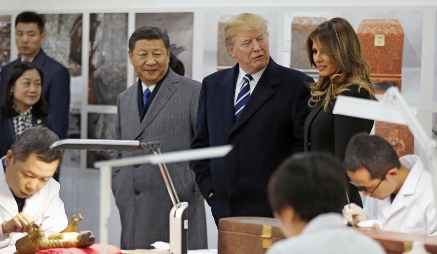 U.S. President Donald Trump, chats with U.S. first lady Melania Trump as they tour the Conservation Scientific Laboratory of the Forbidden City with Chinese President Xi Jinping in Beijing, China, Wednesday, Nov. 8, 2017. (AP Photo/Andy Wong, Pool)