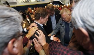 Jack Phillips, owner of Masterpiece Cake, center, is surrounded and prayed for by supporters after a rally on the campus of a Christian college Wednesday, Nov. 8, 2017, in Lakewood, Colo. The small rally was held to build support for Phillips, who is at the center of a case that will be considered by the U.S. Supreme Court in December. The case may determine if business owners like Phillips are having their right of religious liberty and free expression violated by having to offer their wedding services to same-sex couples. (AP Photo/David Zalubowski)