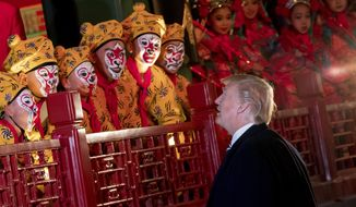 President Donald Trump greets performers following a Chinese opera performance at the Forbidden City, Wednesday, Nov. 8, 2017, in Beijing, China. Trump is on a five country trip through Asia traveling to Japan, South Korea, China, Vietnam and the Philippines. (AP Photo/Andrew Harnik)