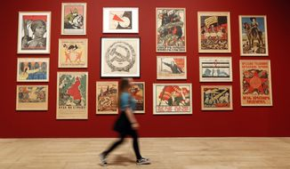 A visitor walks past a wall of Soviet political propaganda posters from around the time of the Civil war 1917-1922, on display at the Tate Modern in the Red Star Over Russia exhibition in London, Tuesday, Nov. 7, 2017. The exhibition is to mark the centenary of the October Revolution, it offers a visual history of Russia and the Soviet Union. (AP Photo/Kirsty Wigglesworth)