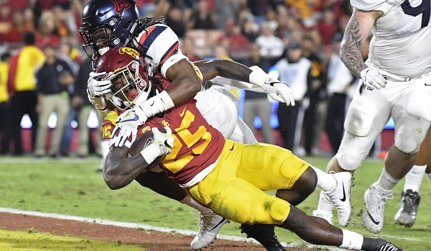 Southern California running back Ronald Jones II, below, dives in for a touchdown while being tackled by Arizona safety Jarrius Wallace during the second half of an NCAA college football game, Saturday, Nov. 4, 2017, in Los Angeles. USC won 49-35. (AP Photo/Mark J. Terrill)