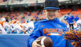 Jackson Bezzant, 8, visits the Boise State sideline at Albertsons Stadium to watch the Broncos play Nevada Saturday, Nov. 4, 2017 in Boise. Jackson was born with Treacher Collins syndrome, a rare condition that affects the development of bones and facial tissues. Earlier this fall a story about Jackson being bullied at school in his hometown of Ammon, Idaho, went viral after his father, Dan Bezzant, took to Facebook to tell his story. (Darin Oswald /Idaho Statesman via AP)