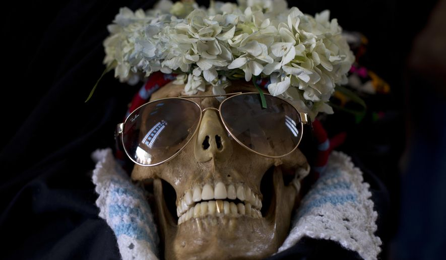 A human skull wearing sun glasses is displayed outside the General Cemetary chapel during the Natitas Festival in La Paz, Bolivia, Wednesday, Nov. 8, 2017. Every year, hundreds of Bolivians carry human skulls adorned with flowers to a cemetery in La Paz, asking for money, health, and other favors as part of a festival. (AP Photo/Juan Karita)