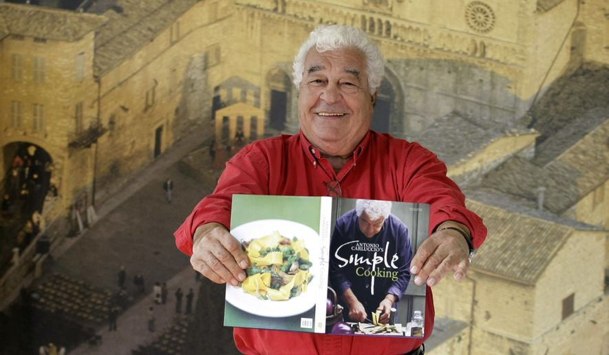 "FILE - In this Tuesday, Sept. 22, 2009 file photo, Italian chef Antonio Carluccio holds a copy of his new cookbook ""Simple Cooking"" as he poses for photographs at a branch of his restaurants, in Covent Garden, London. Celebrity chef and entrepreneur Antonio Carluccio has died, it was announced on Wednesday, Nov. 9, 2017. He was 80. The cause was not immediately revealed. (AP Photo/Matt Dunham, File)"