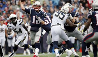 FILE - In this Oct. 29, 2017, file photo, New England Patriots quarterback Tom Brady (12) passes under pressure from Los Angeles Chargers linebacker Melvin Ingram (54) and defensive end Tenny Palepoi (95) during the first half of an NFL football game in Foxborough, Mass. John Elway has measured the Broncos' success against the Patriots both on and off the football field since taking over as head of football operations in 2011. Either the Patriots or Broncos have earned the AFC's top playoff seed every year since with the Patriots winning three conference championships and two Super Bowls and the Broncos winning two AFC titles and one Super Bowl. (AP Photo/Michael Dwyer, File)