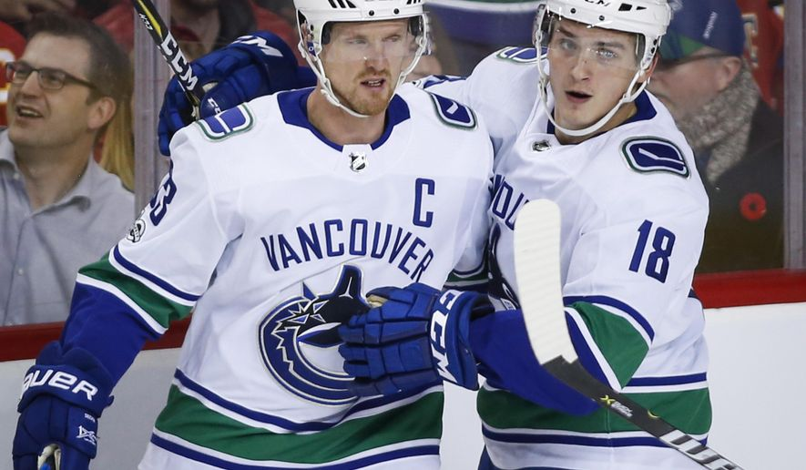 Vancouver Canucks' Henrik Sedin, left, from Sweden, celebrates his goal against the Calgary Flames with Jake Virtanen during the third period of an NHL hockey game Tuesday, Nov. 7, 2017, in Calgary, Alberta. (Jeff McIntosh/The Canadian Press via AP)