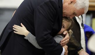 Vice President Mike Pence hugs Evelyn Holcombe at Florseville High School during a stop, Wednesday, Nov. 8, 2017, in Floresville, Texas. A man opened fire inside a church in Sutherland Springs on Sunday, killing and wounding many; Holcombe was in the church during the shooting but escaped. (AP Photo/Eric Gay)