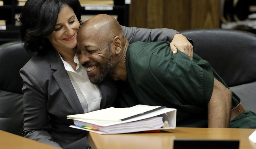 FILE-This Sept. 15, 2017, file photo shows Eric Kelley, right, being hugged by his lawyer Vanessa Potkin moments after Passaic County Superior Court Judge Joseph Portelli granted Kelley a retrial in the case in which he was found guilty of the killing of a video store employee during a robbery in 1993, during a hearing, in Paterson, N.J. Kelly and Ralph Lee, imprisoned for nearly a quarter-century in the killing of a New Jersey video store clerk, have been released on bail to await new trials. Kelley and Lee left the Passaic County Jail on Wednesday, Nov. 8, 2017. Their convictions were overturned after new tests found someone else's DNA on a key piece of evidence. (AP Photo/Julio Cortez, File)