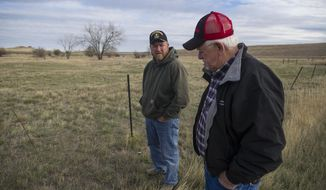 Kelly Guffey, left, and his dad, Willard, talk Firday about the years they lived in the Rawhide Village subdivision. (Ed Glazar/Gillette News Record via AP)