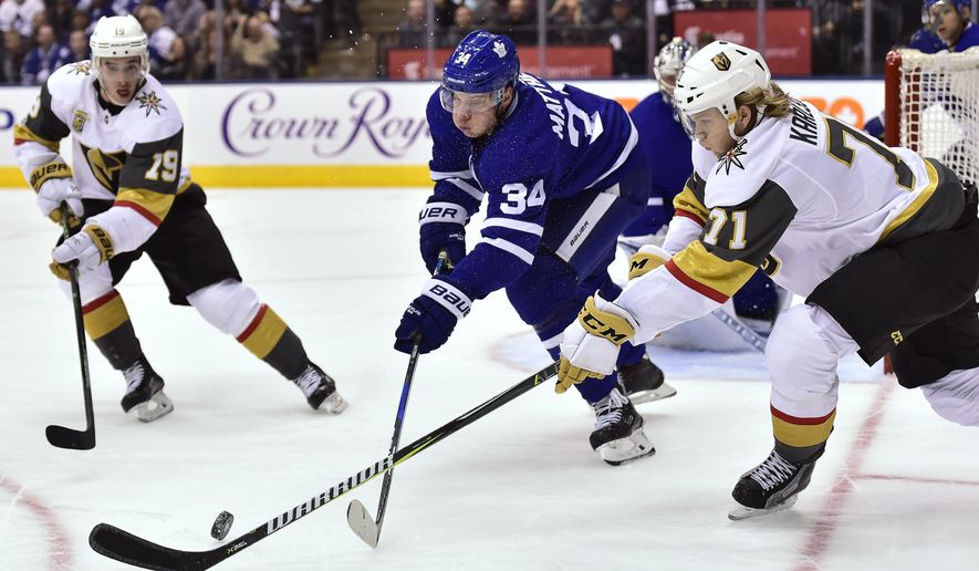 Toronto Maple Leafs center Auston Matthews (34) battles for the puck in the defensive zone against Vegas Golden Knights center William Karlsson (71) and right wing Reilly Smith (19) during the first period of an NHL hockey game, Monday, Nov. 6, 2017, in Toronto. (Frank Gunn/The Canadian Press via AP)