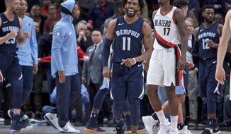 Memphis Grizzlies guard Mike Conley smiles in front of Portland Trail Blazers forward Ed Davis at the end of an NBA basketball game in Portland, Ore., Tuesday, Nov. 7, 2017. The Grizzlies won 98-97. (AP Photo/Craig Mitchelldyer)
