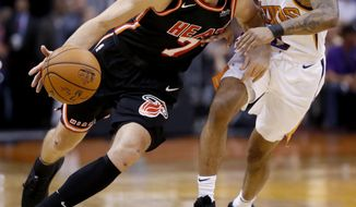 Miami Heat guard Goran Dragic (7) drives around Phoenix Suns guard Tyler Ulis during the first half of an NBA basketball game, Wednesday, Nov. 8, 2017, in Phoenix. (AP Photo/Matt York)