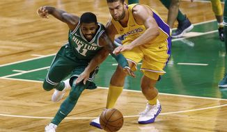 Boston Celtics' Kyrie Irving (11) and Los Angeles Lakers' Brook Lopez reach for the ball during the first quarter of an NBA basketball game in Boston on Wednesday, Nov. 8, 2017. (AP Photo/Winslow Townson)