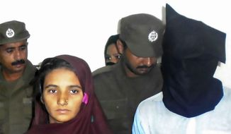 In this Monday, Oct. 30, 2017, photo, Aasia Bibi and her boyfriend, Shahid Lashari, are presented to journalists, at police station in Muzaffargarh in Pakistan. Pakistani police said Wednesday, Nov. 8, 2017, that they arrested a woman for allegedly plotting with Bibi, her newly married niece, to poison the 21-year-old woman's husband with tainted milk that would eventually kill him and 17 other relatives in a remote village. (AP Photo/Iram Asim)