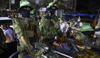 File - In this June 23, 2017 file photo, armed masked militants from the Izzedine al-Qassam Brigades, a military wing of Hamas, stand on a vehicle during a rally marking Al-Quds Day (Jerusalem Day) in Nusseirat refugee camp, in the central Gaza Strip. In comments Wednesday, Nov. 8, 2017, Hazem Atallah, the Palestinian national police commander, cast doubt on whether a reconciliation agreement with the Hamas militant group can be carried out, warning that his forces cannot guarantee law and order unless Hamas disarms in the Gaza Strip. (AP Photo/Adel Hana, File)