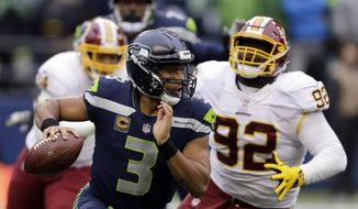 FILE - In this Sunday, Nov. 5, 2017, file photo, Seattle Seahawks quarterback Russell Wilson (3) scrambles away from Washington Redskins defensive end Stacy McGee (92) in the second half of an NFL football game in Seattle. The Seahawks are favored again when they face the Arizona Cardinals on Thursday night. (AP Photo/Stephen Brashear, File) **FILE**