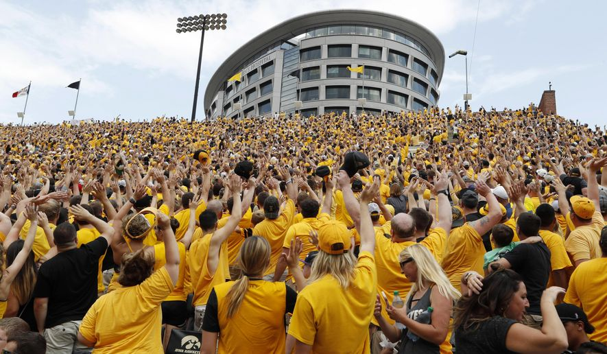 In this Sept. 16, 2017, file photo, Iowa fans wave towards fans watching from University of Iowa's children's hospital at the end of the first quarter of an NCAA college football game against North Texas in Iowa City, Iowa. In the new tradition, known as The Wave, at the end of the first quarter fans in the 70,585-seat Kinnick Stadium turn to wave to the pediatric patients watching from the hospital, a 12-story building that overlooks the stadium from across the street. (AP Photo/Charlie Neibergall, File)