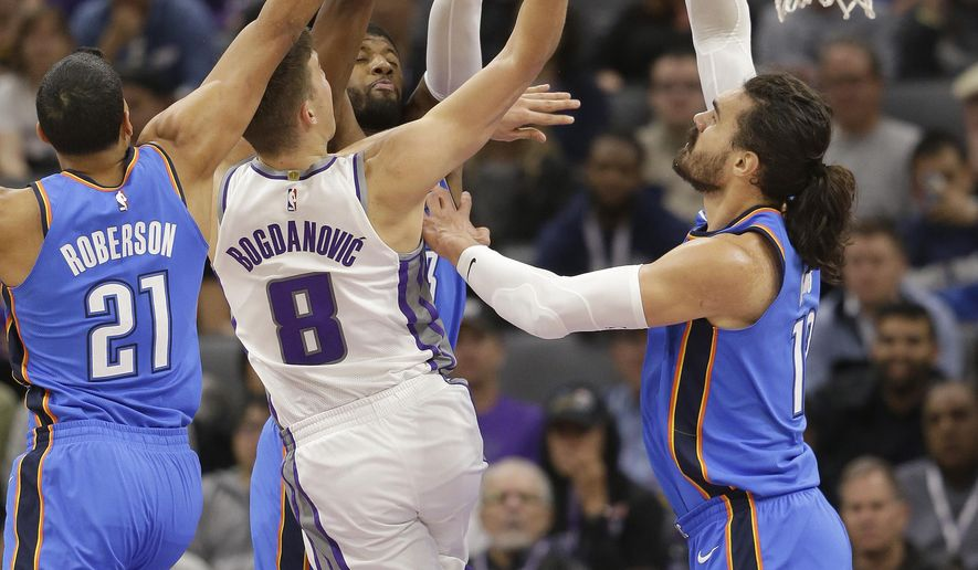 Sacramento Kings guard Bogdan Bogdanovic, center, goes to the basket against Oklahoma City Thunder' Andre Roberson, left, Paul George, third from left and Steven Adams during the first quarter of an NBA basketball game Tuesday, Nov. 7, 2017, in Sacramento, Calif. (AP Photo/Rich Pedroncelli)