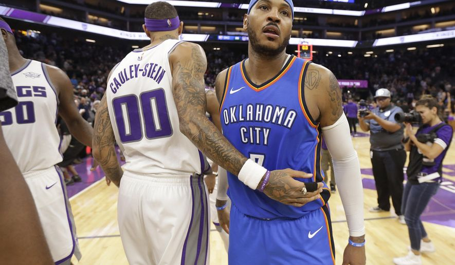 Sacramento Kings center Willie Cauley-Stein, left, and Oklahoma City Thunder forward Carmelo Anthony pass each other after the Kings defeated the Thunder 94-86 in an NBA basketball game Tuesday, Nov. 7, 2017, in Sacramento, Calif. (AP Photo/Rich Pedroncelli)