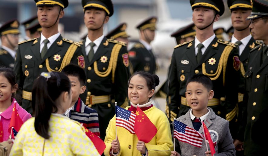 Chinese soldiers and children holding U.S. and Chinese flags line up on the tarmac to greet President Donald Trump as he arrives at Beijing Airport, Wednesday, Nov. 8, 2017, in Beijing, China. Trump is on a five country trip through Asia traveling to Japan, South Korea, China, Vietnam and the Philippines. (AP Photo/Andrew Harnik)