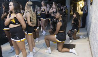 FILE - In this Saturday, Oct. 21, 2017, file photo, Four of the five Kennesaw State cheerleaders who took a knee three weeks ago during the Kennesaw State football game, take a knee once again out of sight of the fans under the visitors' bleachers, during the national anthem before an NCAA college football game between Kennesaw State and Gardner-Webb in Kennesaw, Ga. Kennesaw State, which moved its football cheerleaders inside a stadium tunnel after a group of black cheer squad members knelt during the national anthem, has decided to let them again take the field during pre-game ceremonies. (Kelly J. Huff/The Marietta Daily Journal via AP, File)