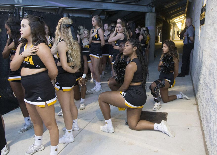 In this Saturday, Oct. 21, 2017, file photo, Four of the five Kennesaw State cheerleaders who took a knee three weeks ago during the Kennesaw State football game, take a knee once again out of sight of the fans under the visitors' bleachers, during the national anthem before an NCAA college football game between Kennesaw State and Gardner-Webb in Kennesaw, Ga. Kennesaw State, which moved its football cheerleaders inside a stadium tunnel after a group of black cheer squad members knelt during the national anthem, has decided to let them again take the field during pre-game ceremonies. (Kelly J. Huff/The Marietta Daily Journal via AP, File)