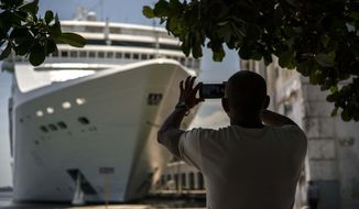 FILE - In this June 17, 2017, file photo, a man takes a photo of a cruise ship in Havana harbor, Cuba. President Donald Trump announced a new policy in June that partially rolled back the recent diplomatic opening with Cuba. New regulations implementing that policy are being unveiled Wednesday.  (AP Photo/Ramon Espinosa, File)