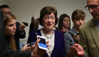 Sen. Susan Collins, R-Maine, is surrounded by reporters as she heads to go vote on Capitol Hill in Washington, Tuesday, Nov. 7, 2017. (AP Photo/Susan Walsh)